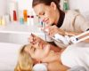 Woman getting tweezing eyebrow by beautician.