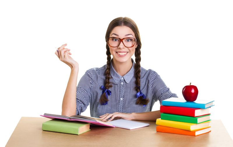 smiling student  girl sit from wooden table, holding pen and look at camera, near lie big red apple and pile of books, white background